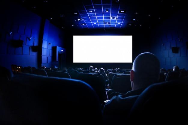 Cine o teatro en el auditorio. la gente que mira una película.