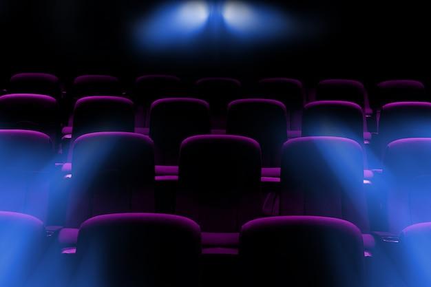 Cine vacío con asientos de color púrpura con destellos de luz del proyector
