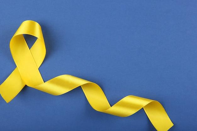 Cinta amarilla que simboliza el cáncer en la vista superior de los niños