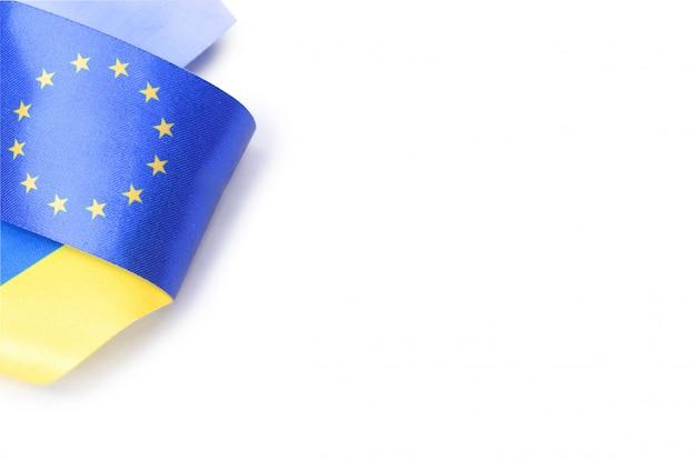 Cinta con banderas de la unión europea y ucrania aisladas sobre fondo blanco.