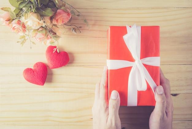 Cinta blanca del arco de la caja de regalo a mano y corazón con la flor en la opinión superior del fondo de madera de la tabla.