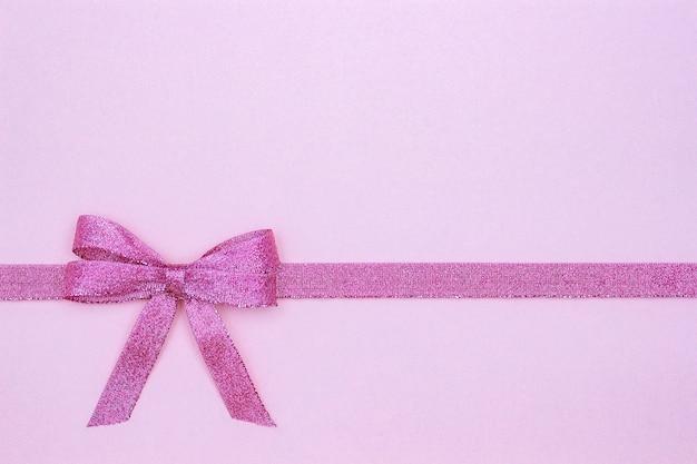 Cinta brillante decorativa con el arco en fondo rosado.