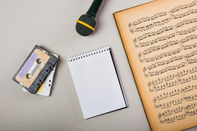 Cinta de casete; bloc de notas en espiral y micrófono con una vieja libreta musical vintage.