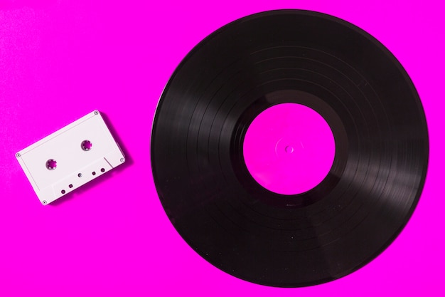 Cinta de cassette blanca audio y disco de vinilo en fondo rosado