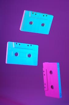 Cinta de cassette estilo vintage suspendido en el aire sobre fondo morado