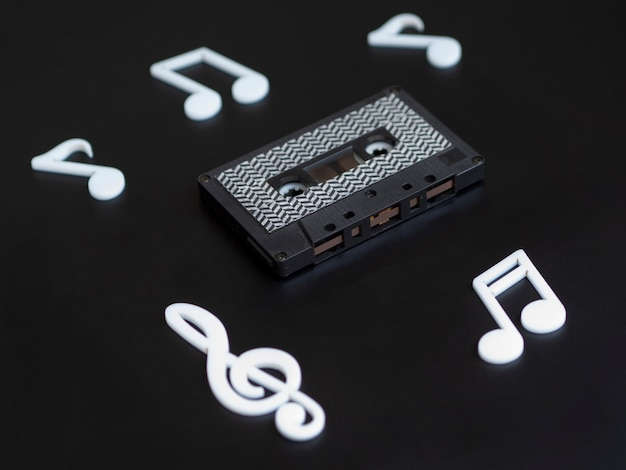 Cinta de cassette negra sobre fondo oscuro con notas