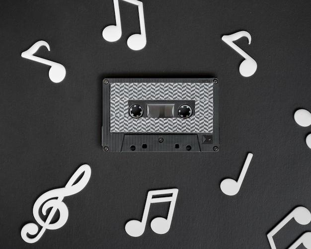 Cinta de cassette oscura con notas musicales blancas que la rodean