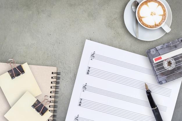 Cinta de cassette de la pluma de la hoja de la música y café con leche latte en la tabla de madera