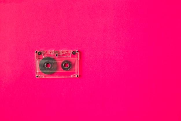 Cinta de cassette transparente sobre fondo rosa