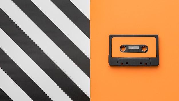 Cinta de cassette vintage sobre fondo naranja y rayas