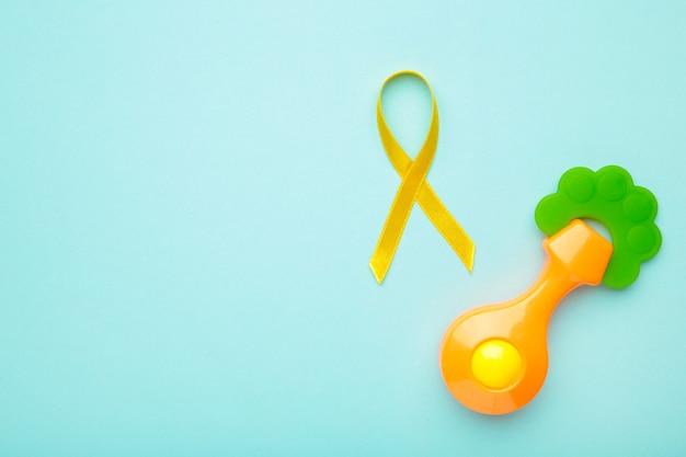 Cinta de conciencia amarilla y juguete para niños sobre fondo azul pastel con espacio de copia.