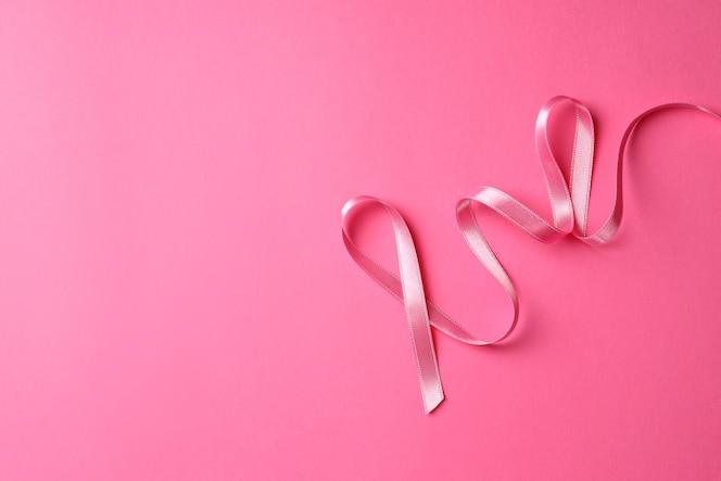 Cinta de concienciación sobre el cáncer de mama sobre fondo rosa