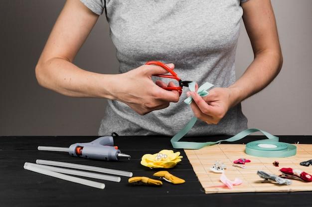 Cinta de corte de mujer con tijera durante la fabricación de varios pinza de pelo