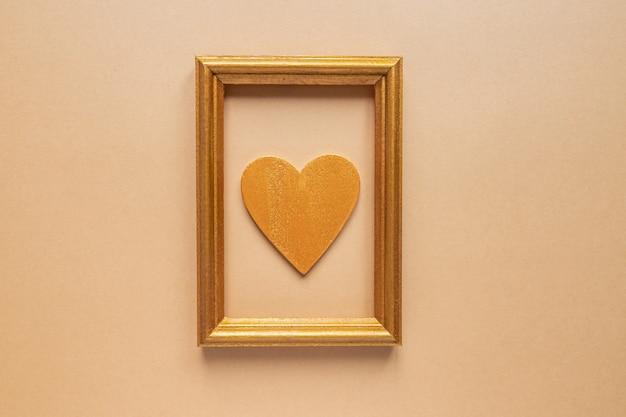 Cinta decorativa trenzada y marco de fotos dorado con corazón de madera.