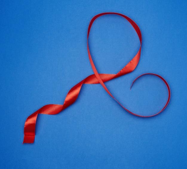 Cinta delgada de seda roja retorcida sobre un fondo azul, color clásico de moda