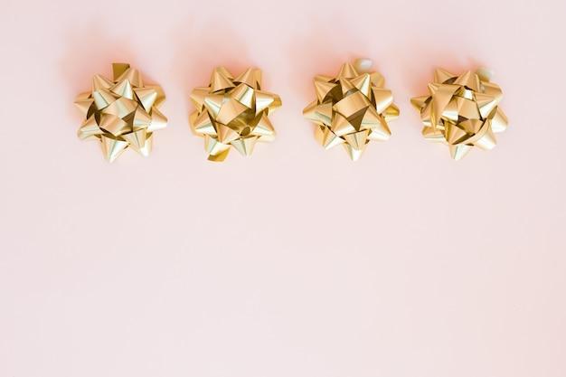 Cinta dorada con lazo sobre fondo pastel. envoltura de caja de regalo, materiales de envoltura. presenta preparación copia espacio