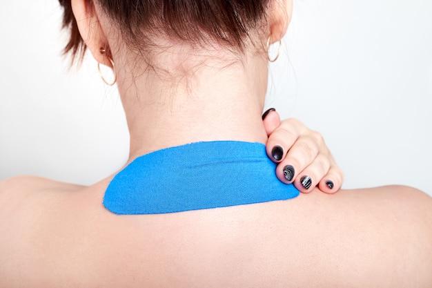 Cinta especial de fisio en la espalda de una mujer joven.