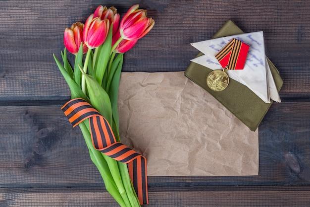 Cinta de george, papel de nota, flores rojas letras de primera línea, gorra militar y órdenes en el fondo de madera. día de la victoria o el concepto del día del defensor de la patria.