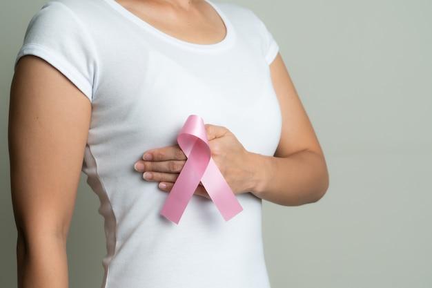 Cinta insignia rosa en la mano de la mujer tocando el pecho para apoyar la causa del cáncer de mama. concepto de concienciación sobre el cáncer de mama
