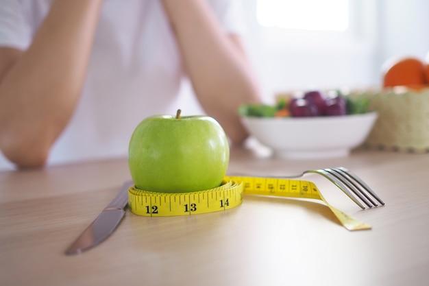 Cinta métrica alrededor de la manzana verde. a continuación hay ensalada de leche y verduras en la mesa de madera.