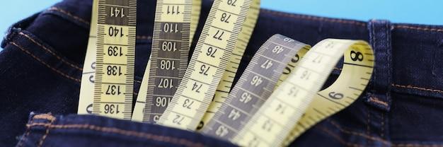 La cinta métrica amarilla está en el bolsillo de los pantalones vaqueros closeup