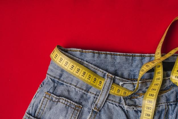 Cinta métrica amarilla en la cintura en lugar de un cinturón en jeans sobre un fondo rojo.