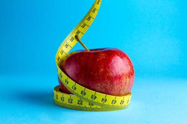 Cinta métrica amarilla y una manzana