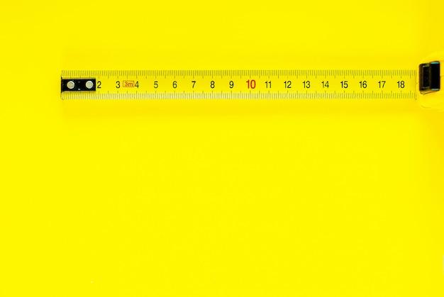 Cinta métrica amarilla sobre fondo amarillo. copia espacio