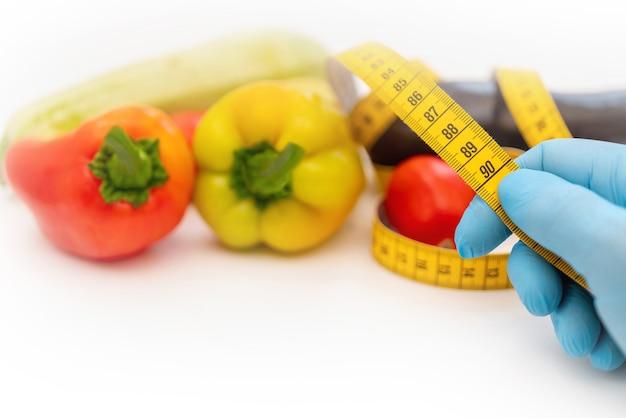 Cinta métrica amarilla y verduras.