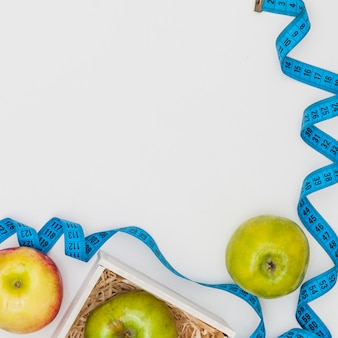 Cinta métrica azul con manzanas rojas y verdes aisladas sobre fondo blanco