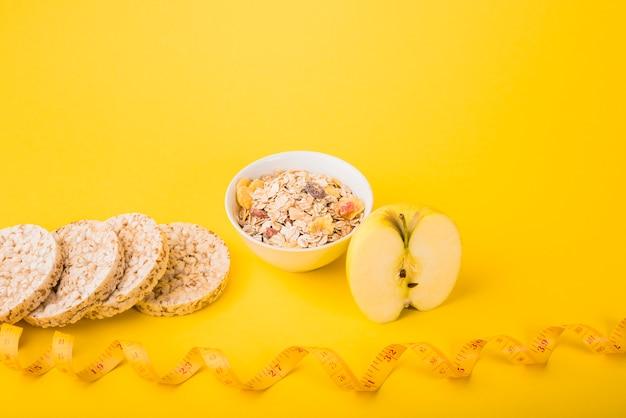 Cinta métrica cerca de fruta, pan crujiente y tazón de muesli