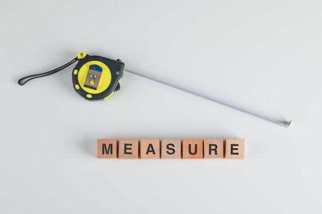 Cinta métrica y cubos de madera con la medida de texto