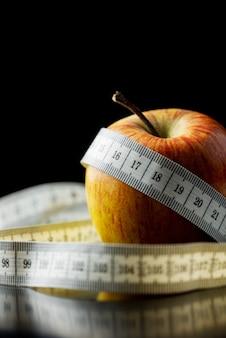 Cinta métrica envuelta alrededor y manzana en una imagen conceptual de dieta y pérdida de peso. sobre fondo negro.
