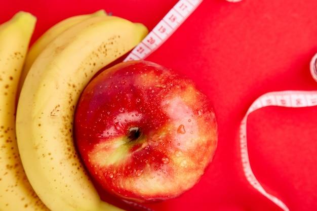 Cinta métrica envuelta alrededor de una manzana roja y plátano