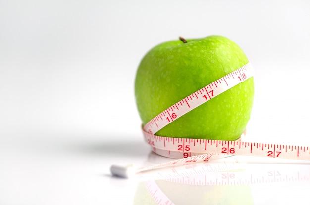 Cinta métrica envuelta alrededor de una manzana verde como símbolo de la dieta.