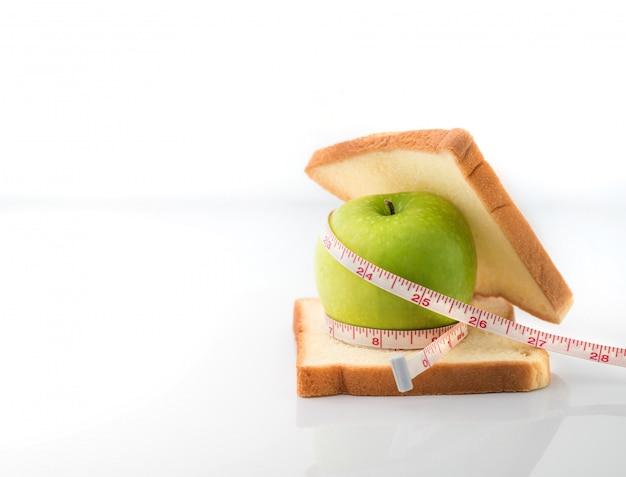 Cinta métrica envuelta alrededor de una manzana verde con una rebanada de pan blanco como símbolo de la dieta