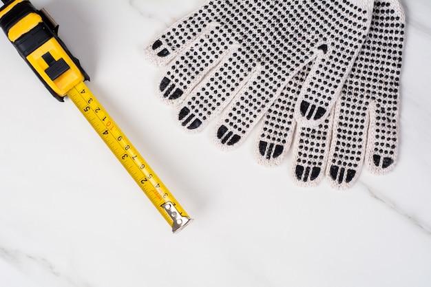 Cinta métrica y guantes.
