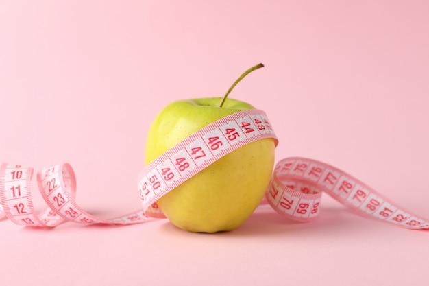 Cinta métrica con manzana, pérdida de peso.