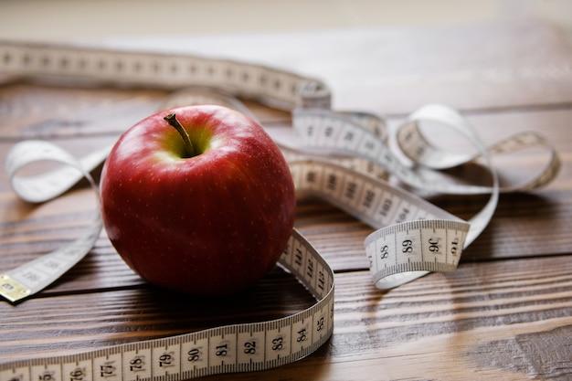 Cinta métrica y manzana roja. el concepto de dieta, estilo de vida saludable y nutrición adecuada.