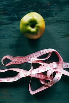 Cinta métrica de manzana y rosa, concepto de pérdida de peso