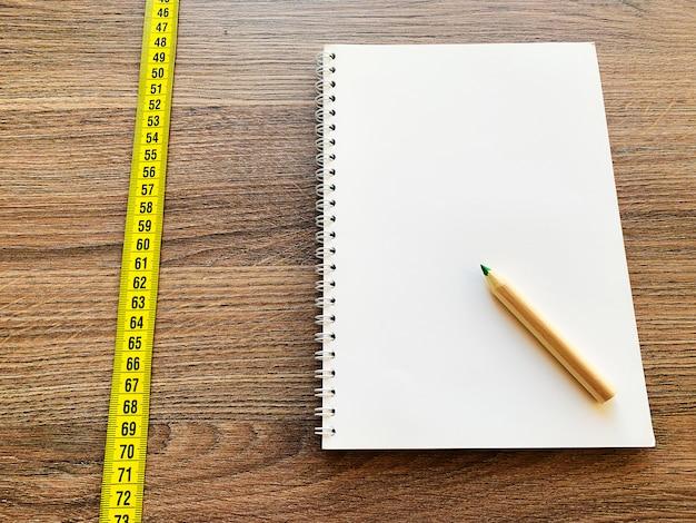 Cinta métrica en mesa de madera con bloc de notas diario