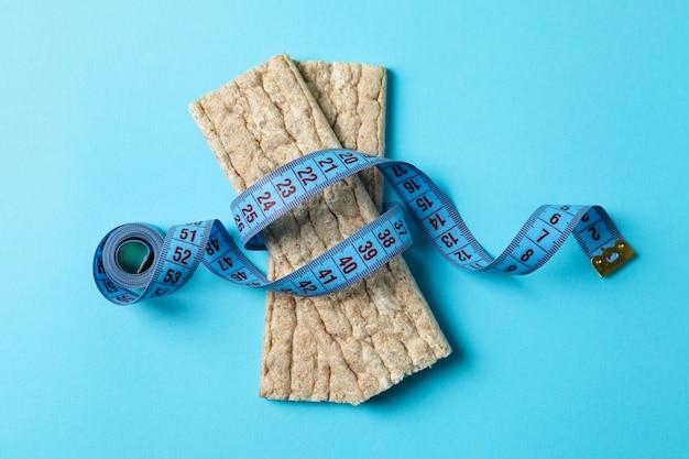 Cinta métrica y pan dietético sobre fondo azul.