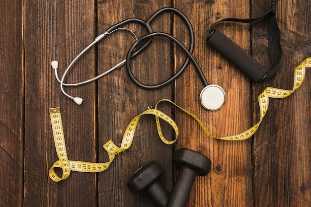 Cinta métrica; pesa; estetoscopio y correa de fitness sobre fondo de madera