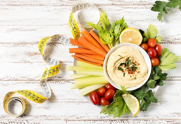 Cinta métrica con plato de hummus y verduras.