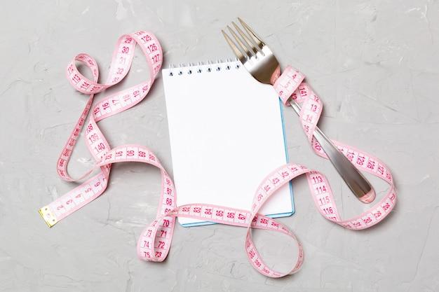 Cinta métrica rosa, cuaderno abierto y tenedor