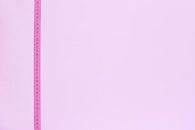La cinta métrica rosada cruza verticalmente el fondo rosado.
