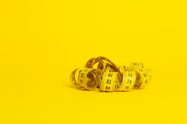Cinta métrica sobre un fondo amarillo. cinta métrica en forma de espiral retorcida sobre un fondo amarillo. concepto de dieta y adelgazamiento, espacio de copia