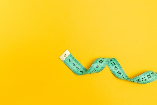 Cinta métrica sobre un fondo amarillo. dieta, adelgazamiento, concepto de obesidad.