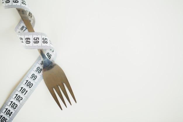 Cinta métrica y un tenedor en blanco