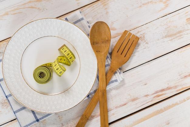 Cinta métrica, utensilios de cocina de madera y un plato.